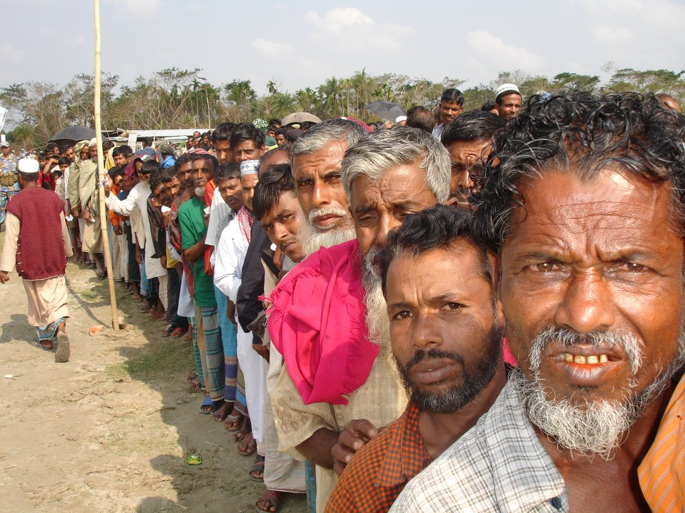 Men in the village of Boro Bighai, southwestern Bangladesh, line up for government assistance after Cyclone Sidr slammed into the country on 15 November. More than 3,000 people were killed and millions left homeless.