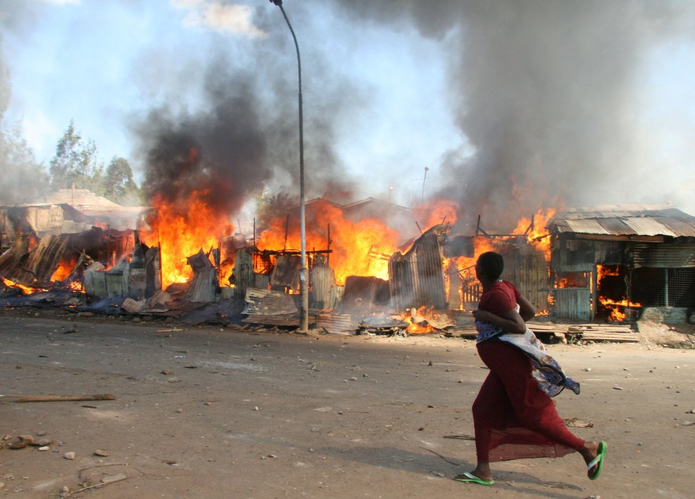 A Pregnant woman runs past burning shacks in Nairobi's Mathare slum during post-election violence. [31 December 2007]