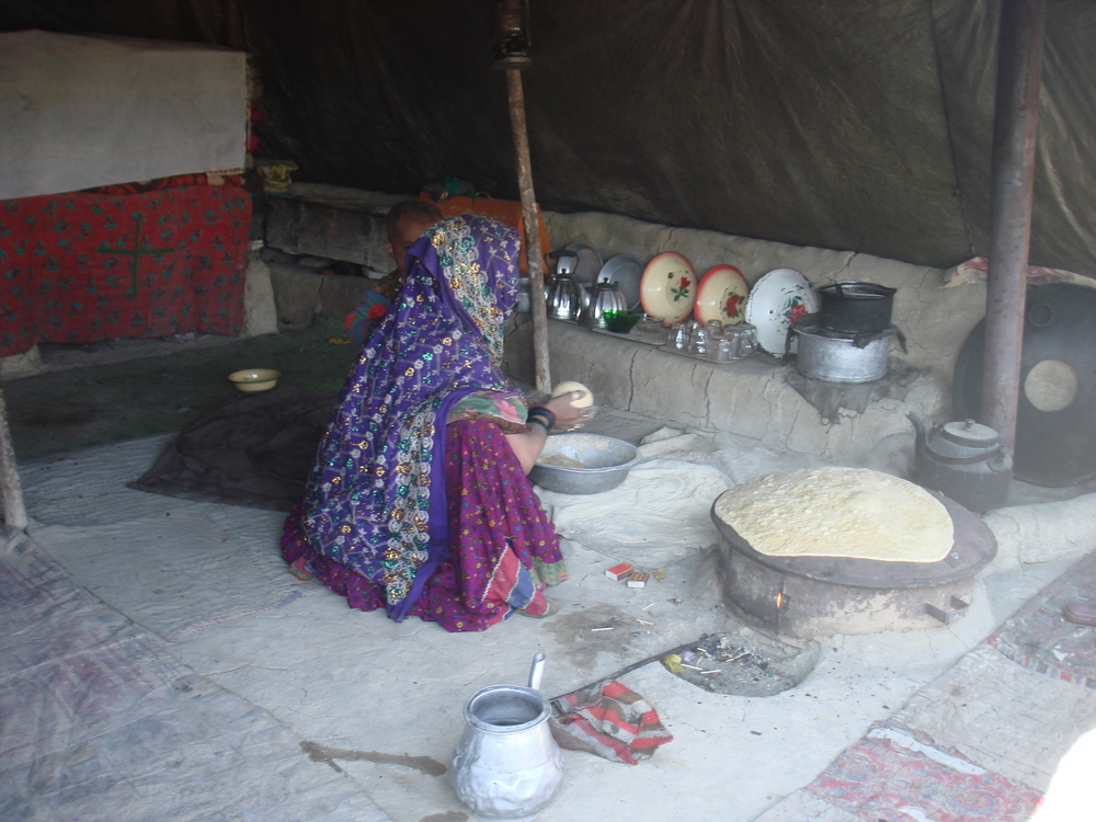 Caption: More than two million Afghans have recently been pushed into food insecurity due to soaring food prices. A Kochi (nomad) woman is baking bread under a tent in southern Kandahar province.