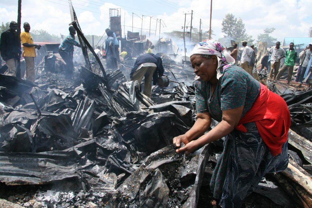 A woman tries to salvage the little that is left of her property in Mathare slums after most properties were set a blaze. Kenya, January 2008.