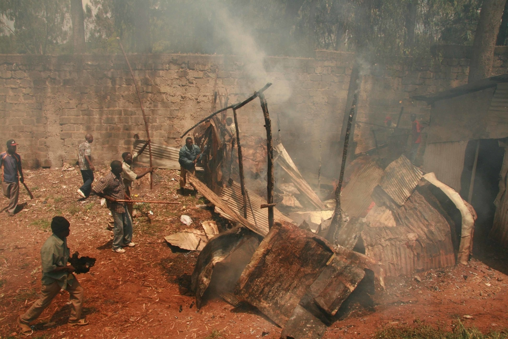 Angry youth put off a fire that had been set by rival groups after violence broke out in parts of Kibera, Nairobi, Kenya. January 2008. Kibera has been divided into ethnic boundaries with violence breaking out when the two sides meet.
