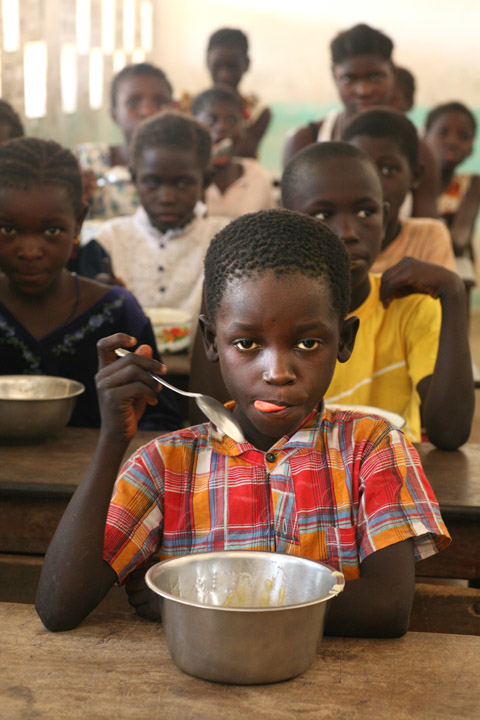 a boy eats donated food by WFP in a classroom in Eva Orango school in Orango Island of Bijago Archipelago in Guinea-Bissau Feburary 2008. According to World Food Programme (WFP) intellectual levels rise when children are fed properly.