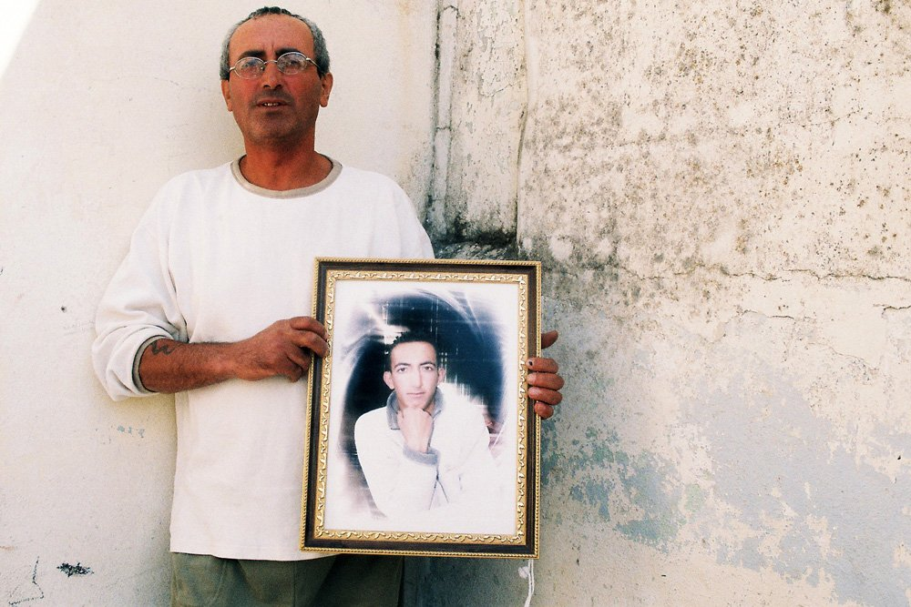 A Palestinian man holds up a picture of his son who is being held in an Israeli jail.