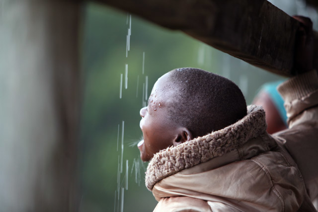 A young boy drinks rain water at the displaced camp in Eldoret, Kenya, April 2008. The heavy downpour brings a risk of waterborne diseases that can hit the camp.