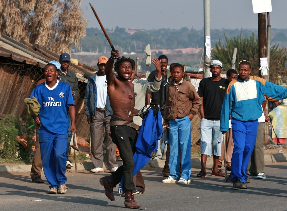 Residents of Ramaphosa informal settlement in Reiger park near Benoni east of Johannesburg took to the streets again waving sticks, knives and axes as they continue to hunt down beat and kill foreigners around the area. South Africa. May 2008