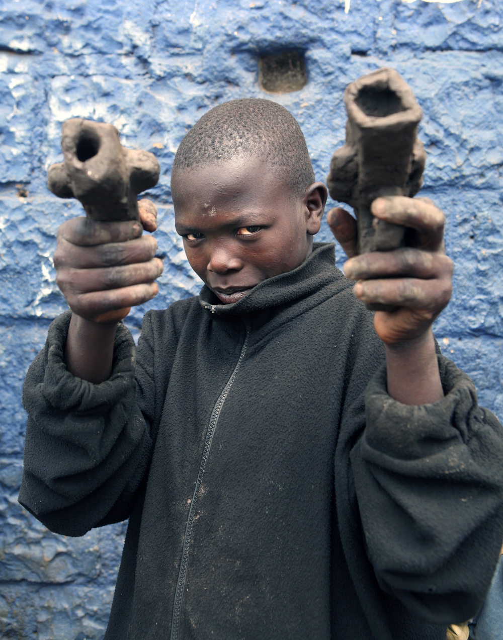 A boy plays with mud pistols in Mathare slum of Nairobi. Mathare Valley is one of the five large slums in Nairobi Kenya and one of the most dangerous slums