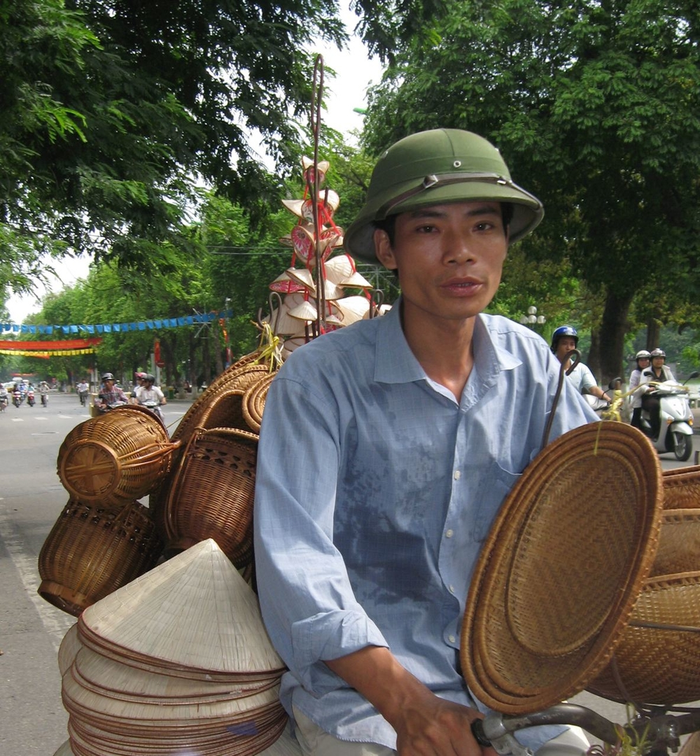 A bicycle vendor carries dozens of baskets for sale through the streets of Hanoi.