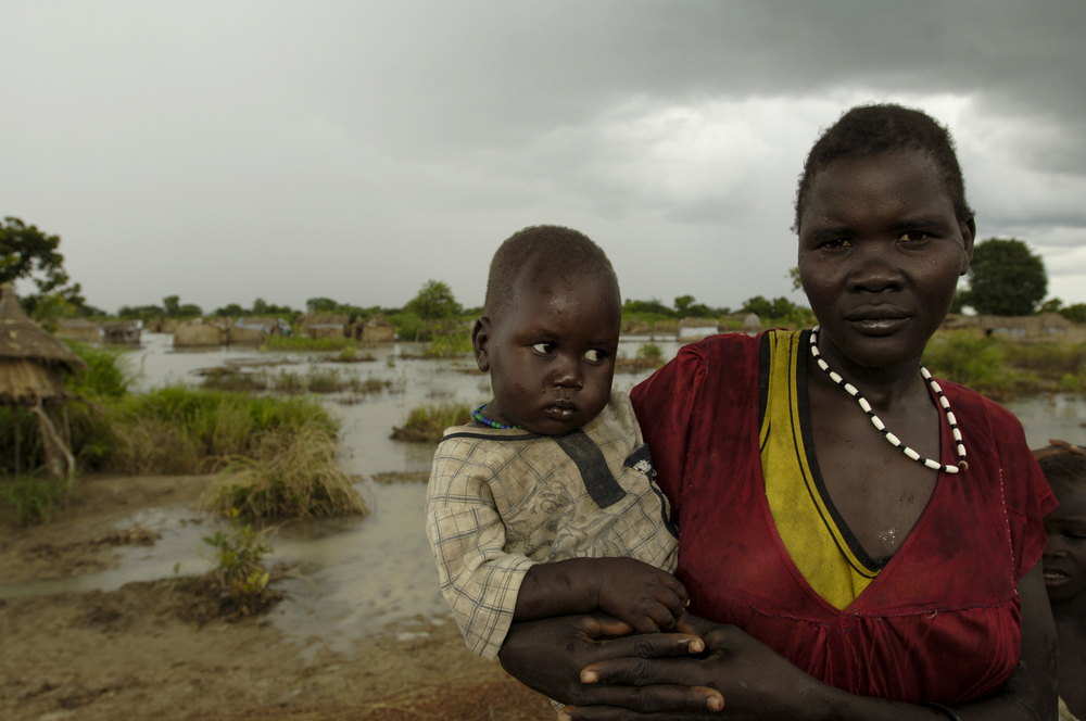 Displaced residents living by the roadside next to their flooded tukuls. Sudan. August 2008. Extremely heavy early rains inundated the areas around Aweil with floodwaters, displacing thousands of residents.  UN agencies and NGOs working with their governm
