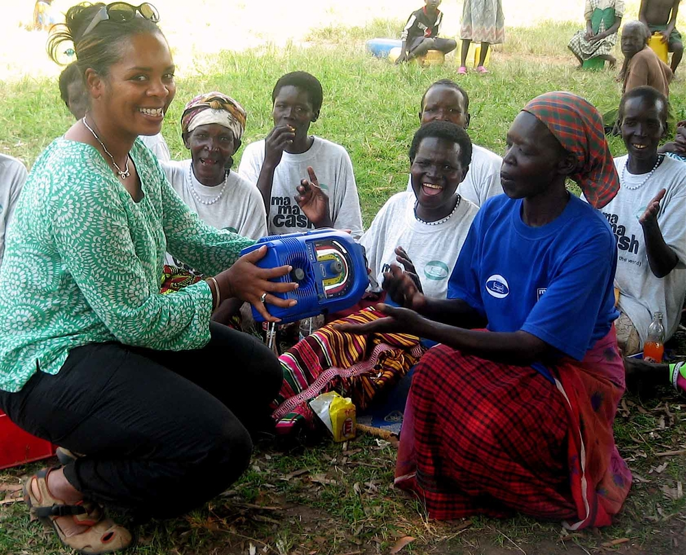 IRIN Radio's producer Jackie Christie hands a wind-up radio to women in Unyama camp, Gulu district, northern Uganda, so they can listen to the radio drama they helped write and dramatize.
