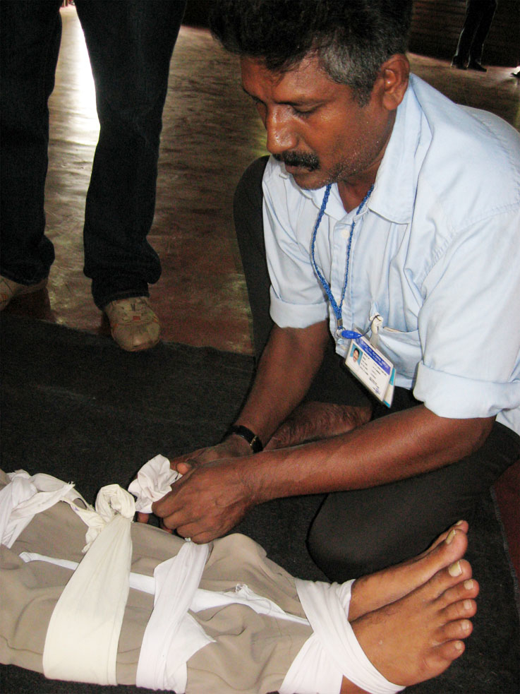 A tuk-tuk driver practices tying a splint on someone's leg. Health professionals hope training taxi drivers will prevent  injuries caused to accident victims while being transported to hospital.
