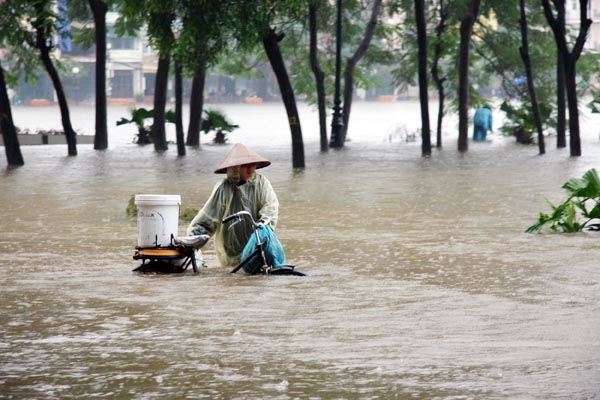 A woman caught in flooding in Hanoi. The Vietnamese capital has been inundated with some 20 inches of rain over a three-day period leaving 19 dead. In northern Vietnam, at least 44 people are dead and 100,000 homes underwater.