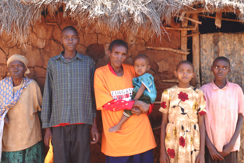 Mbula Waema (holding child), with some of her children and her mother-in-law, Mary Mwelu, 90 (left), at their home in Kathonzweni, Makueni
