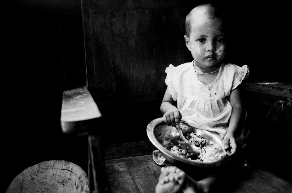 A young child eats from a bowl in Myanmar's badly affected Ayeyarwady Delta