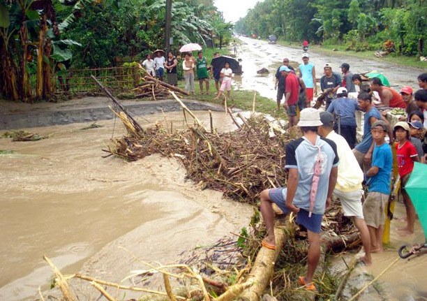 Pigcawayan, Mindanao - Villagers gather on a highway in the southern Philippine town of Pigcawayan as floodwater that swamped the road bring debris. About 160,000 families have been displaced in the southern island of Mindanao due to flash floods caused b
