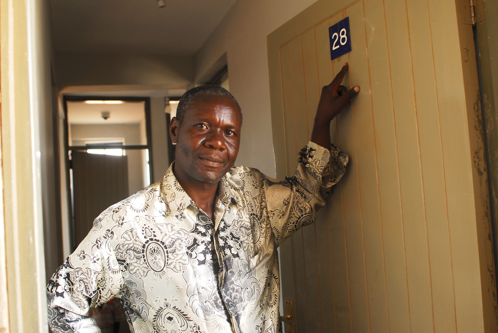 Pius Okello points at the number at the entrance of his new home in the New Highrise Estate, put up by the government and UN-HABITAT under the Kenya Slum-Upgrading Programme