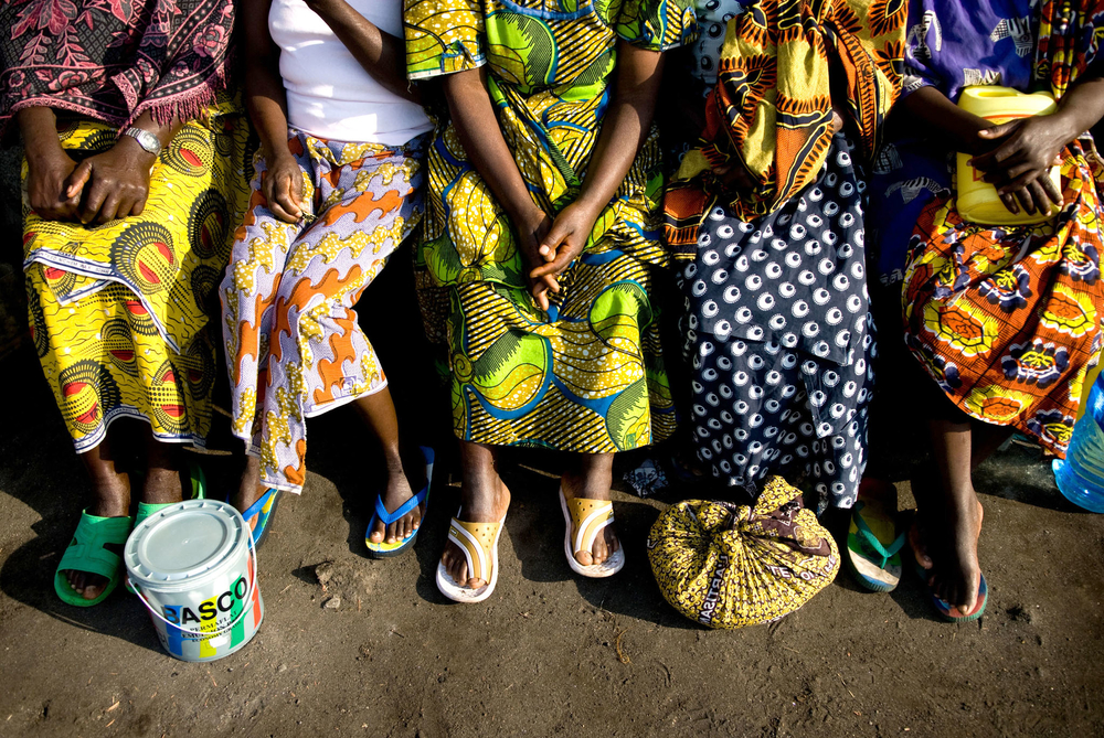Women sit together outside their dormitory at the Heal Africa Transit Center for women victims of sexual violence. While these women have received humanitarian and medical assistance for their immediate needs after sexual violence, due to funding gaps the