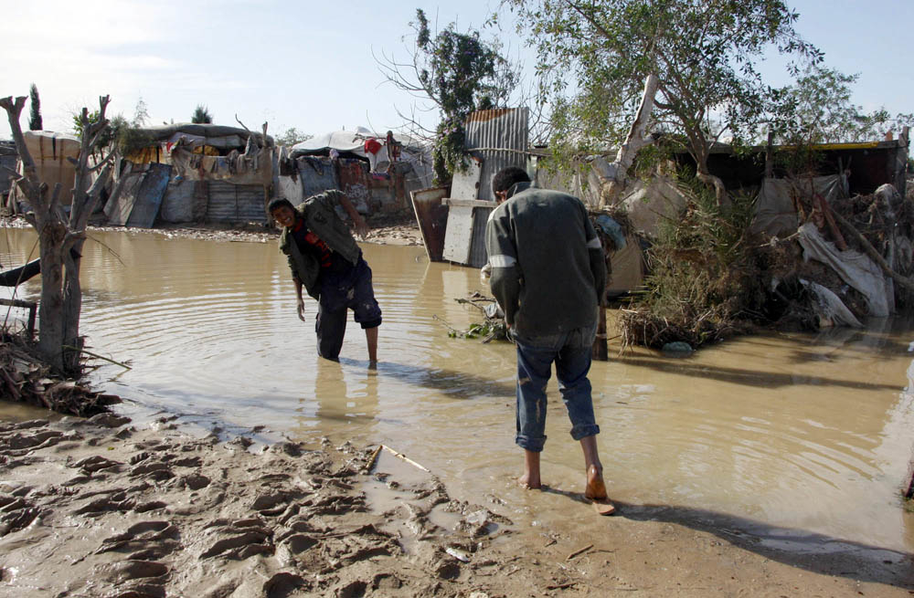 Muhamed al Kawayda (left), 11, and his brother Saber, 14, walk through a flooded street in al-Mughraqa, a town 6km southwest of Gaza City