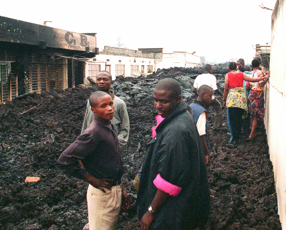Residents of Goma in eastern Democratic Republic of Congo make their way through lava-filled streets after a nearby volcano, Mount Nyirabongo, erupted in January 2002, destroying much of the town