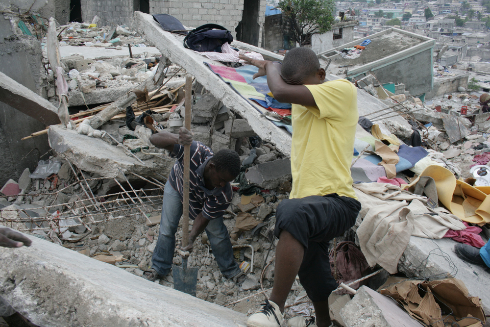 Young men search for bodies in the neighbourhood of Fort National in Haiti's capital Port-au-Prince. March 2010