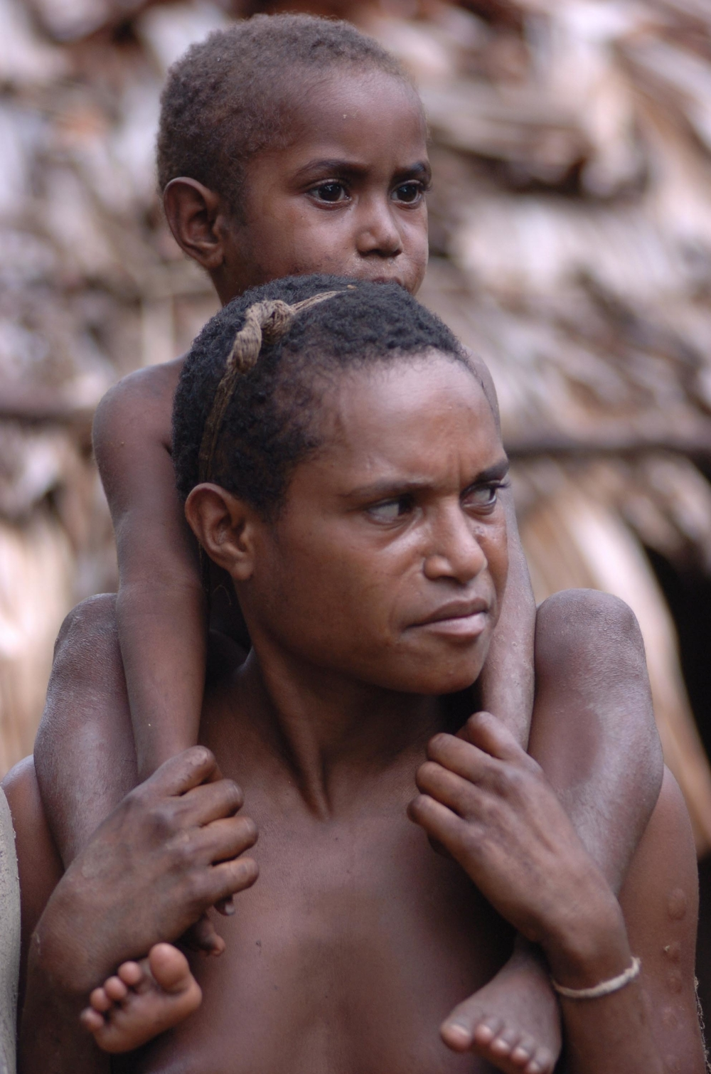 A Papuan woman carrying her son in Papua. The region is one of Indonesia's poorest. Approximately 35 percent of the Papua's 2.6 million inhabitants live below the poverty line