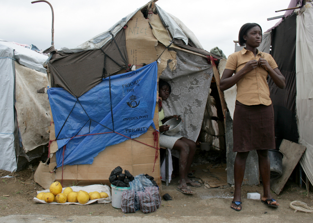 Young women at Jean-Marie Vincent camp for displaced families in Port-au-Prince sell charcoal and fruits. March 2010