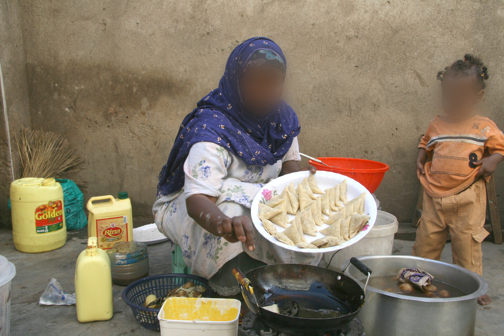Asha Abdul* (not her real name), prepares samosas for sale outside her house in Eastleigh. Unregistered urban refugees like Abdul prefer to pay for services such as road repair so as not to draw attention to their illegal status