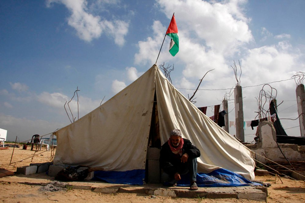 An old man sits outside his UNRWA-supplied tent in the Ezbet Abed Rabbo area of northern Gaza. His home was destroyed in the war