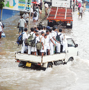 Children hitch a ride to their school in Colombo, At least three people are known to have died due to heavy flooding in of western and southern Sri Lanka [18 May 2010]