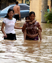 Manila - Two women and a child navigate a flooded street in suburban Pasig City east of Manila at the height of tropical storm Ketsana in 2009