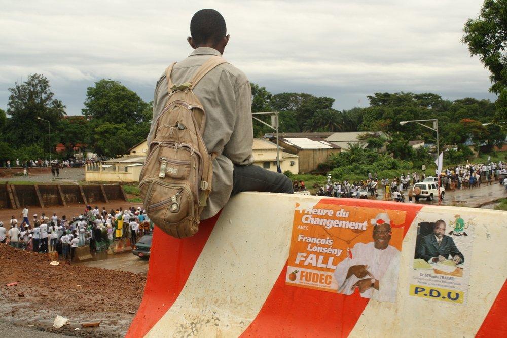 Youth watches in the Guinea capital, Conakry, a presidential candidate's rally days ahead of 27 June poll