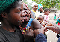 A baby, held by his mother, cries as he receives a vaccine injection at a mobile outreach point in Zimbabwe's Masvingo District during the country's 2009 measles immunization drive