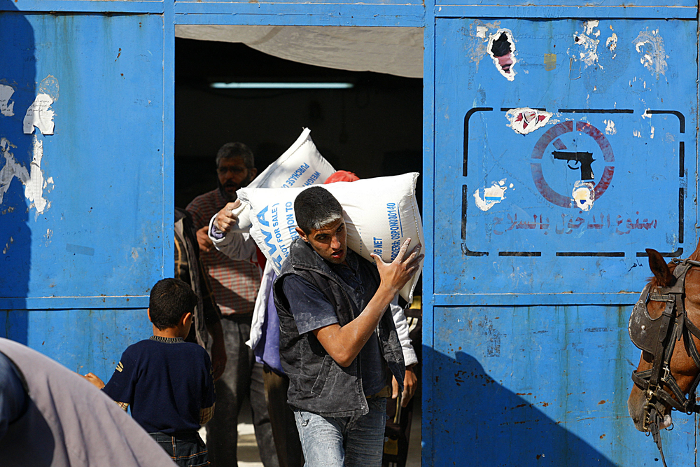 A Palestinian aid worker carries a bag of flour at a United Nations food distribution center in Shati refugee camp