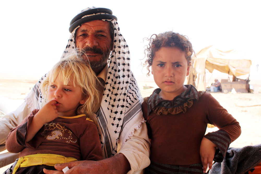 Shepherd Abdul Rahim Bsharat, 59, holds his two youngest daughters, Samoud, three (blonde) and Assia, five. The Bsharat family have lived and farmed in al-Hadidiya village in the West bank since the 1960s