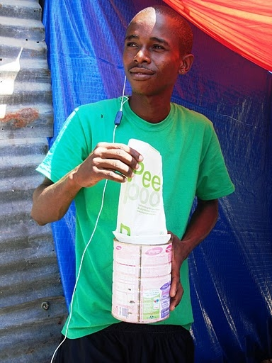 Resident of an IDP settlement in the Delmas area of Port-au-Prince receives a week's supply of biodegradable plastic bags being tested as toilets