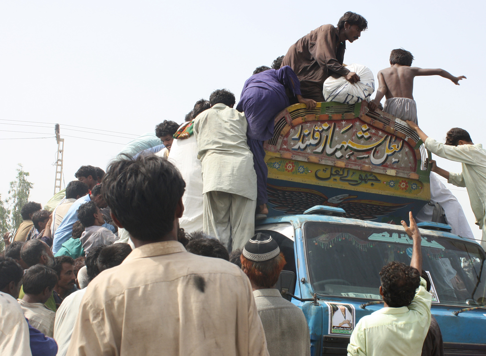Frustrated people displaced by the floods climb a food aid truck in Makli town in the Sindh province