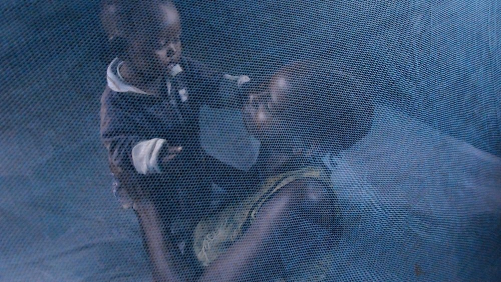 Mother and child under a mosquito net. Malaria. For generic use