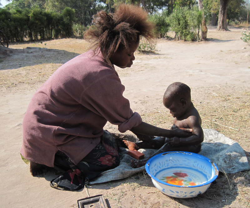 A young mother bathes her baby in Luapula Province, northern Zambia