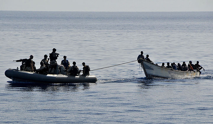 US Navy personnel tow a disabled skiff carrying 52 Somali migrants. Gulf of Aden