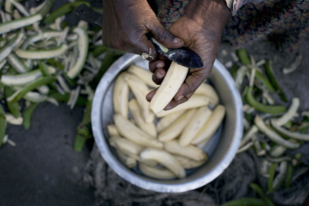 A woman cooks a meal for her grandchildren outside her home  in Kasese, Uganda. For generic use, food security