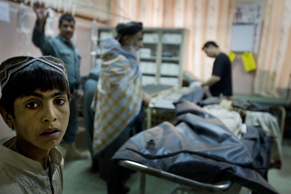 A young boy in a doorway at Mirwais Hospital, Kandahar, October 2010, after a male civilian was brought in - dead on arrival