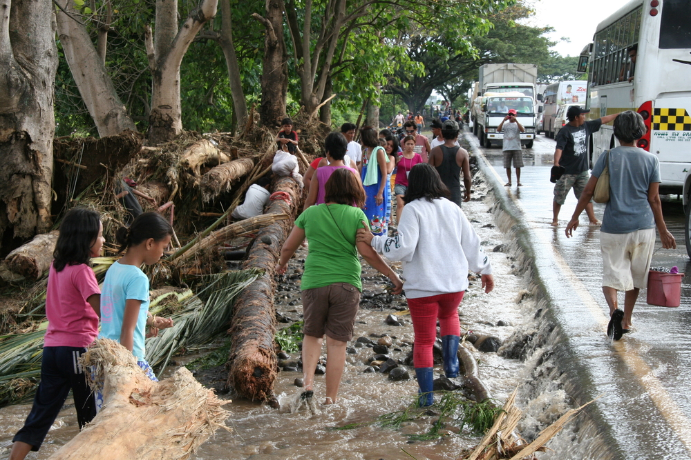 Residents traverse receding flood waters and debris following a flash flood that struck a village in Davao del Sur Province, southern Philippines on 20 January 2010. At least three people drowned in the province