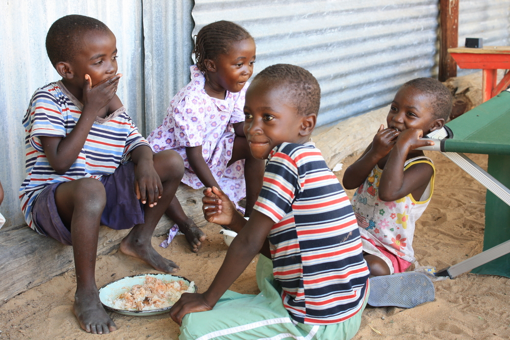 Children in the Haukongo household share their food