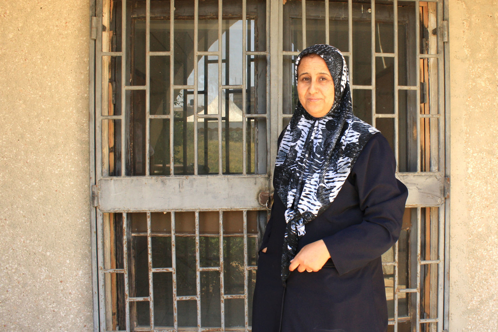 Zainab al Beidi opens a locked gate to the swimming pool that was never completed.