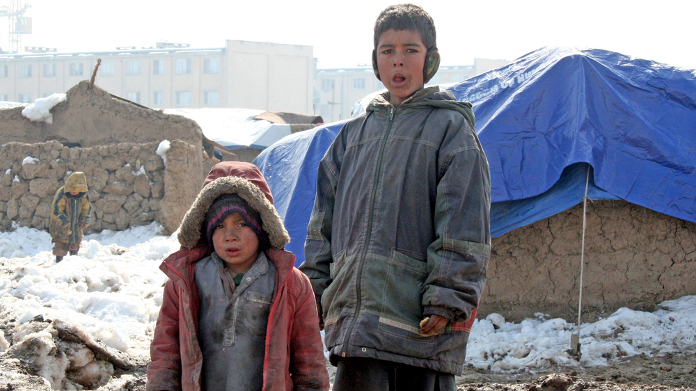 Two IDP children from southern Helmand province standing behind their mud hut on the outskirts of Kabul