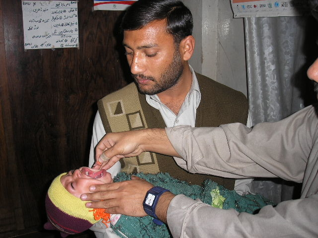 A child receives polio drops as a desperate struggle continues to contain the virus