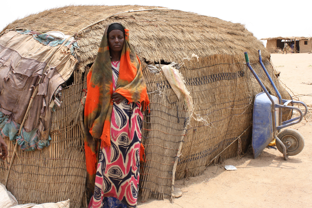 Maria Farah outside her ari, which her family of six shares with their calf and goat in Ethiopia