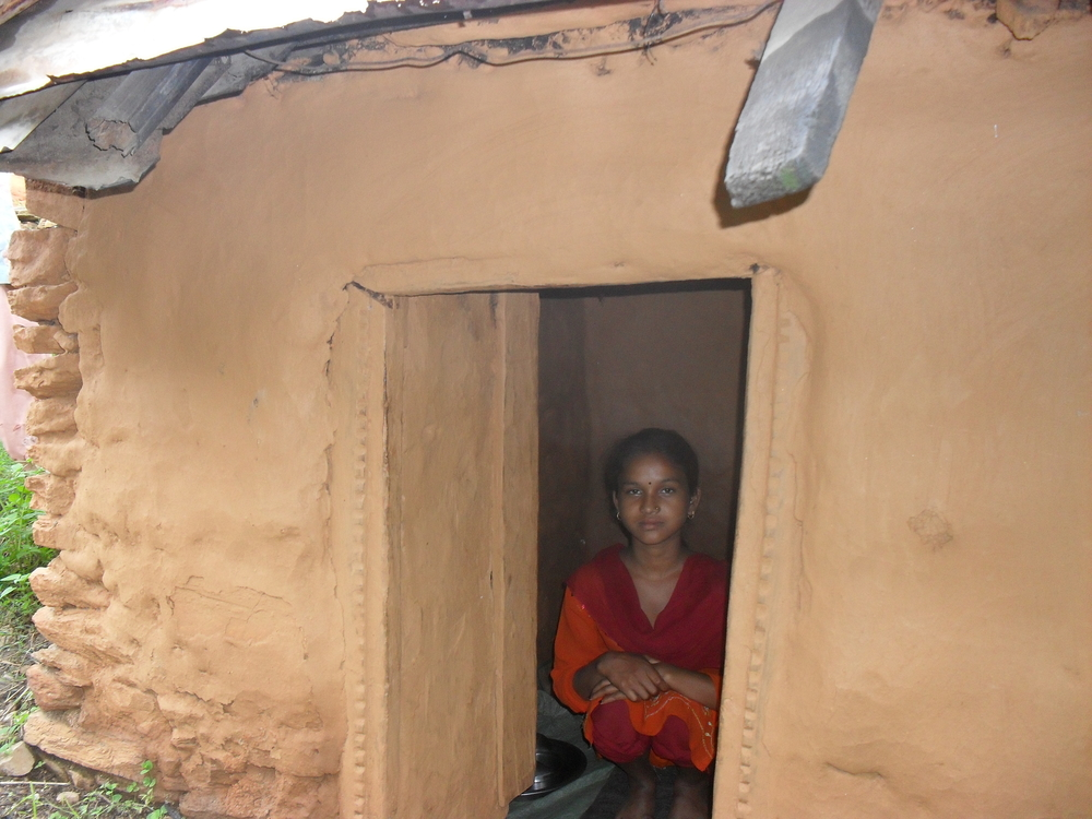 Kamala Vishwarkarmas sits inside her goth, where she has been staying alone during the week of her monthly period.  'Chhaupadi', the Nepalese practice of segregating menstruating women from their houses and men, was outlawed by Nepal's supreme court in