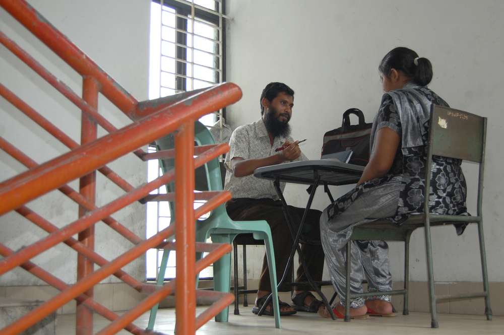 A psychotherapist provides counseling to a patient near the stairs of a hospital for lack of space