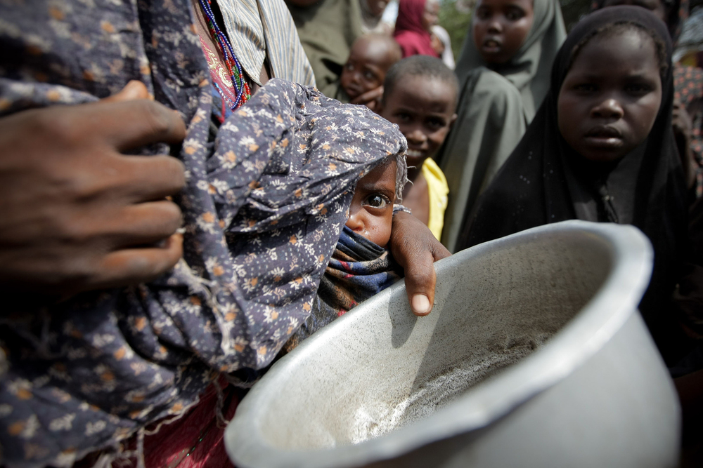 A woman holding her young malnourished baby queues for food at the Badbado camp for Internally Displaced Persons (IPDs)