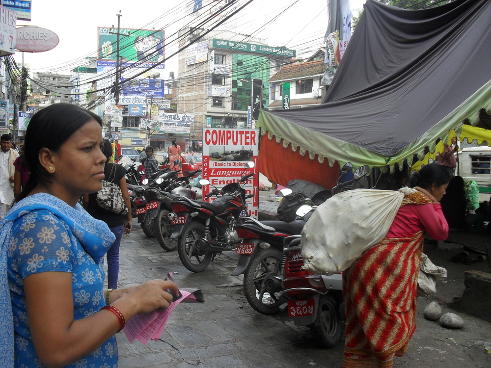Ranita Chaudhary, a staff member of Sankalpa, passing out flyers about the constitution outside their groups's tent in Kathmandu. Women's rights groups feel left out of the negotiations for Nepal's next constitution